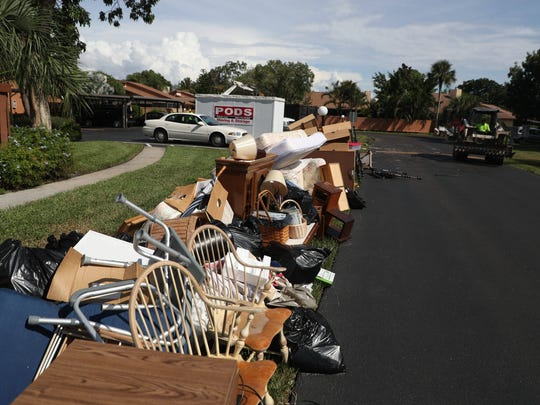 Crews work to get rid of belongings and trash that was destroyed in recent flooding at the Royal Woods community of Island Park.
