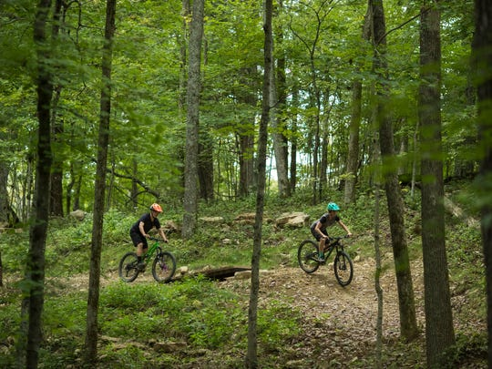 On Your Left Cycle's Derek Fetko, left, and Parklands' program coordinator, Ali Greenwell, take a lap down Crazy Red's trail, a more advanced trail path, at the new Parklands Silo Bike Center in Turkey Run Park. Sept. 11, 2017