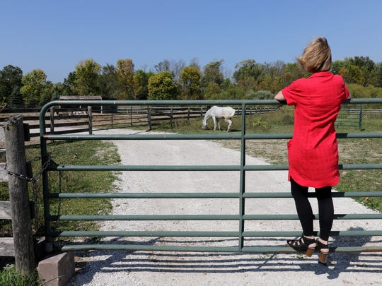 Polly Schellinger tries to attract the attention of one of her horses on the Healing Farm where she practices Reflexology and  produces more than 100 products using aromatics and essential oils.