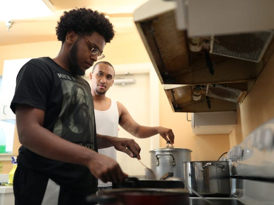Olivier Etiennr, left, a FAMU sophomore, and Bobby Washington, a senior, cook dinner for their housemates at one of the three Southern Scholarship Foundation buildings on the university's campus. The foundation is celebrating its 20th year of establishing free housing on the school's campus.