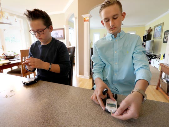 Brayden, 10, and Jacob, 13, Merton use their glucometers