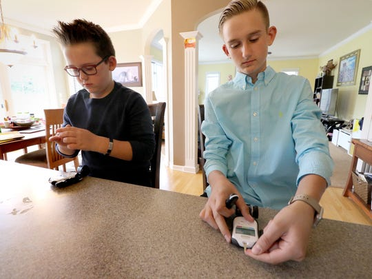 Brayden, 10, and Jacob, 13, Merton use their glucometers to check their blood sugar levels at their Hartland home.  All three if the Merton children are living with Type 1 Diabetes.