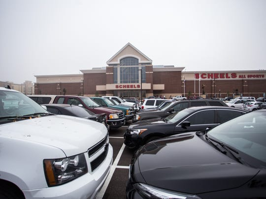 Cars fill the parking lot of Scheels sporting goods store.