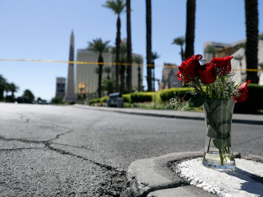 Flowers are placed near the scene of a mass shooting at a music festival near the Mandalay Bay resort and casino, top left, on the Las Vegas Strip, Monday, Oct. 2, 2017, in Las Vegas.