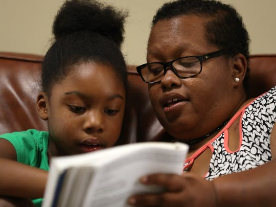Brandi Leland who finished her treatment for breast cancer with radiation therapy this July, works with her duaghter Lillian, 6, on a reading lesson at the Thomasville Road Baptist Church on Sept. 27, 2017. Leland homeschools five of her six children, which includes outings on three days of the school week to music sessions and group co-op language courses.