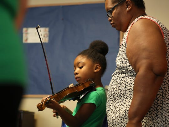 Brandi Leland who finished her treatment for breast cancer with radiation therapy this July, works with her duaghter Lillian, 6, as she plays the violin during music study at the Thomasville Road Baptist Church on  Sept. 27, 2017. Leland homeschools five of her six children, which includes outings on three days of the school week to music sessions and group co-op language courses.