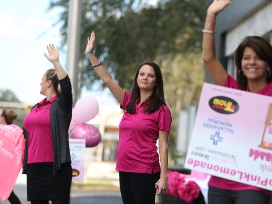 Amy Hume, from left, Brittany Wyman and Pam Monnier wave to passing cars from their lemonade stand outside of the Hotel Duval, part of Breast Cancer Awareness Month activities around town on Wednesday, Oct. 4, 2017.