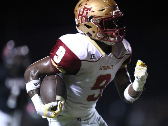 Florida High's Will Haigler runs the ball against North