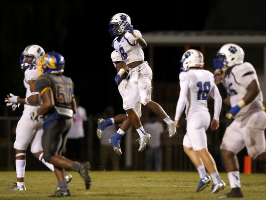 Godby's Treon Patrick Jr. and Jaylen Key celebrate an interception against Rickards during their game at Cox Stadium on Friday night.