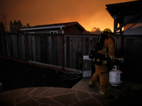 A firefighter removes a propane gas tank in an evacuated residential area as wildfires continue to burn on Saturday in Santa Rosa.