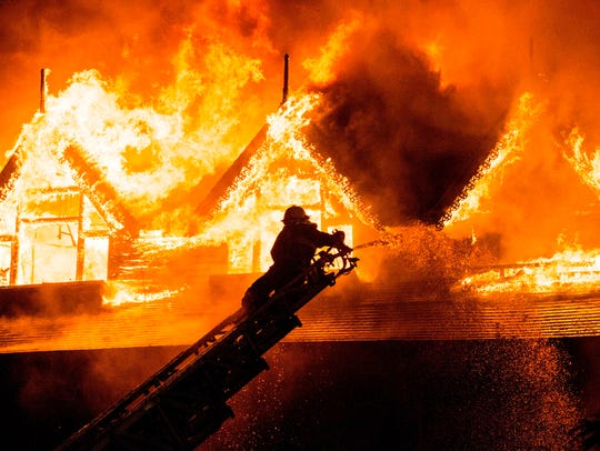 A firefighter extinguishes a fire at Kandawgyi Palace