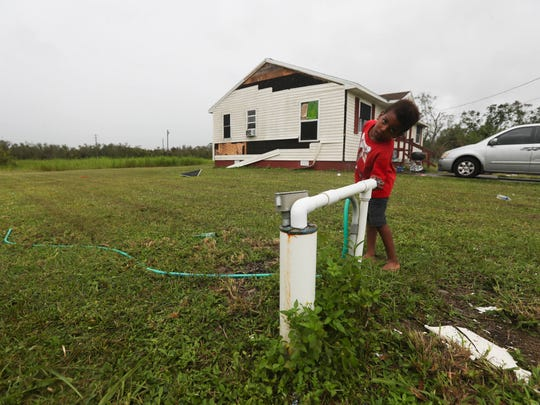 Kani Bolden turns off the well water at his grandmother's Charleston Park home.