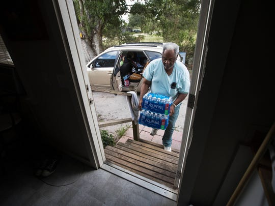 James Ford carries in bottled water for Charleston