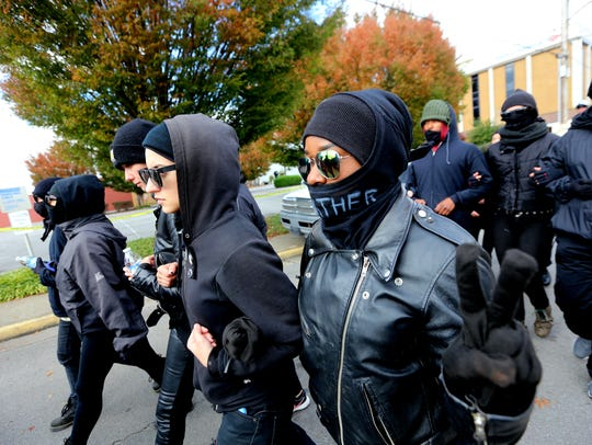 Antifa members march arm in arm to the White Lives