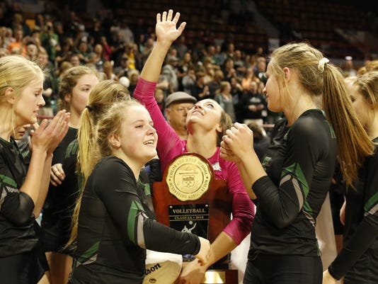 Fossil Ridge senior, Lauren Rice, looks to sky with tears in her eyes as she holds the 5A State Championship trophy, Nov. 12 at the Denver Coliseum. Fossil Ridge defeated Mountain Vista 3-2. Photo by Philip B. Poston