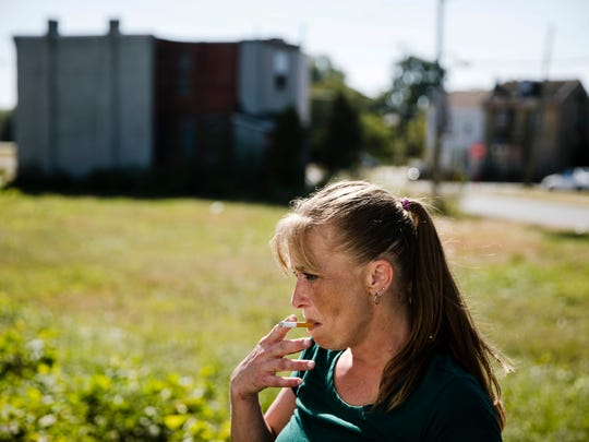 Denise Brown who is addicted to heroin, smokes as after she picked up a package of necessities from the Camden Area Health Education Center Mobile Health Van parked in vacant lot in Camden, N.J.