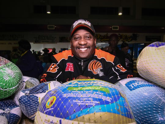 Norman Oliver poses with frozen turkeys during the