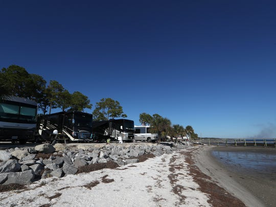 Campers park along the sand at the Ho Hum RV Park in