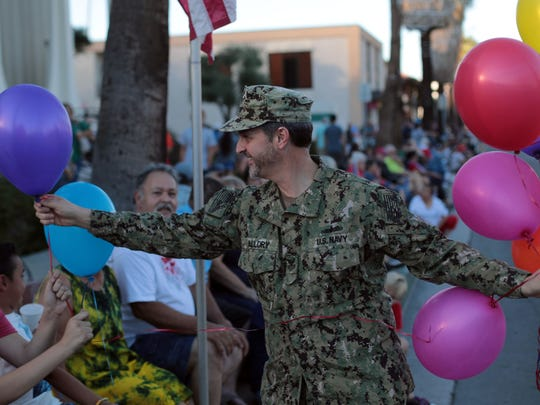 US Naval serviceman Marshall Mallory, of La Quinta, and member and teacher passes out balloons during the Palm  Springs Veterans Day Parade on Saturday, November 11, 2017 in Palm Springs.