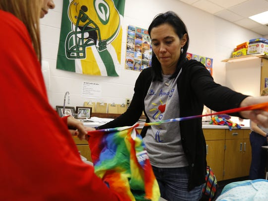 Kara Weiland, right, rips a piece of cloth from a tie-dye shirt during the Be Amazing meeting Friday, Nov. 10, 2017, at D.C. Everest Middle School in Weston.