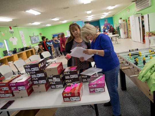 Rio del Sol Kiwanis members Bernadette Alarid, left, and Jill McQueary look over a list before handing out shoes Friday at the Hilltop location for the Boys & Girls Clubs of Farmington.