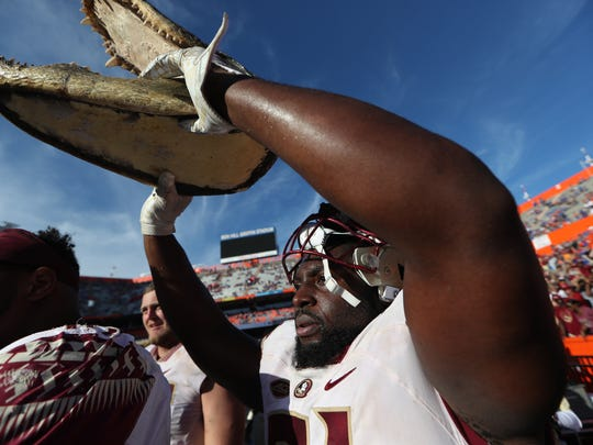 FSU's Derrick Nnadi holds up a gator head in celebration of the Seminoles 38-22 win over Florida at Ben Hill Griffin Stadium in Gainesville on Saturday.