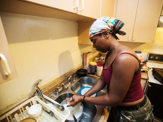 Christal Bolden washes dishes for a Charleston Park resident recently. The water in the home has tested positive for coliform bacteria and extremely high salinity levels. Because of recent stories in the News-Press, Lee County along with the health department is testing as many wells as possible in the community.