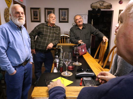 Twins Henry (left) and Joe Gutmann and Peter Laundre talk with long-time friends and customers Cheryl and James Oliva of Pewaukee at the Two Brothers Winery tasting bar.