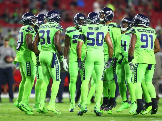 Seattle Seahawks players huddle together in their color