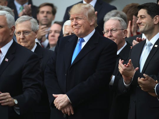 President Donald Trump, flanked by Republican lawmakers, celebrates Congress passing the Tax Cuts and Jobs Act with Republican members of the House and Senate on the South Lawn of the White House on Wednesday,