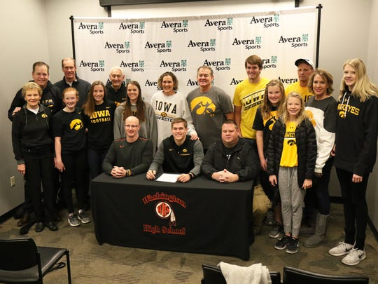 Seth Benson of Washington High poses with his family and coaches on Friday at the Avera Sports Institute after signing a national letter to play at Iowa.
