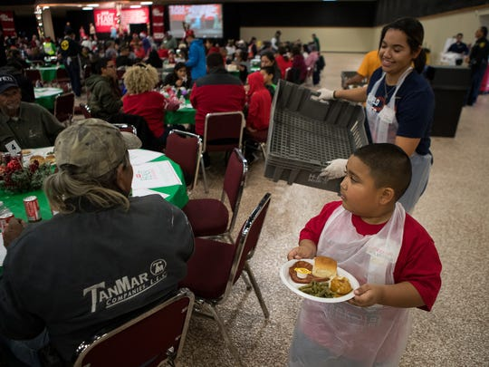 Donovin Deleon, 7, helps serve food during the 29th Annual H-E-B Feast of Sharing at the American Bank Convention Center Exhibit Hall on Saturday, Dec. 23, 2017.