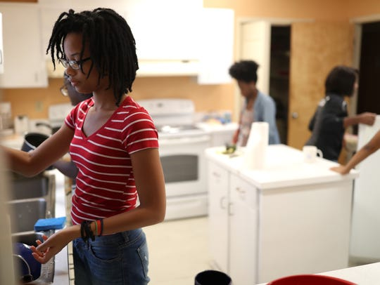 Medgie Leger, a freshman at FAMU cleans up after dinner