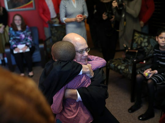 Chief Judge Jonathan Sjostrom embraces a 7-year-old boy after presiding over his adoption ceremony on Christmas day at the Big Bend Community Based Care office.