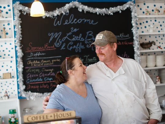 """Sacramento natives Larry Monson, right, and his with Malana embrace in their My Little Bakery & Coffee Shop opened less than two weeks prior, an effort Monson describes as to """"put one more brick into the foundation for a better town, to bring some life back,"""" Thursday, Dec. 14, 2017, in Corning, Ohio. (AP Photo/John Minchillo)"""