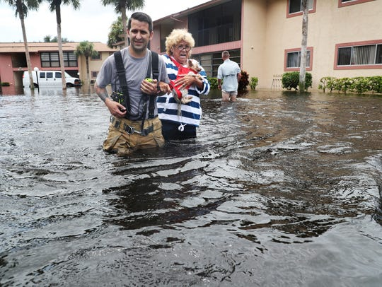 San Carlos Fire Department's Matthew Graham rescues Sheila Crosby and her dog, Jesse, from her flooded home in the Royal Woods neighborhood of Island Park in south Lee County.