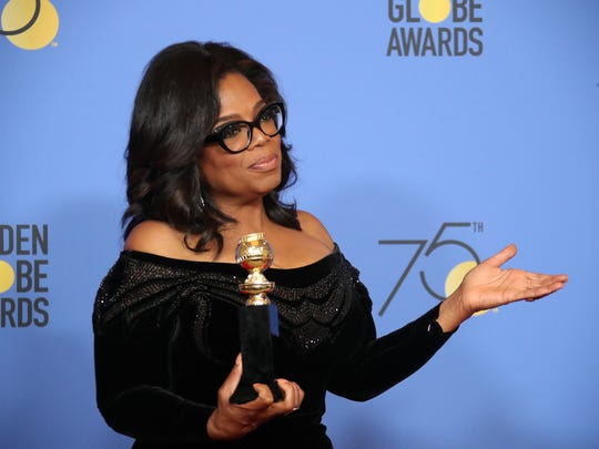 Oprah Winfrey holds the Cecil B. DeMille award backstage