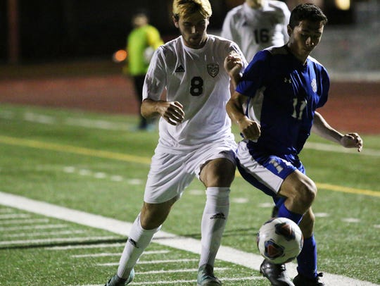 Naples defender Hugh Wilkinson, left, fights for possession with Barron Colier's Michael Rodriguez during the Golden Eagles' match with Barron Collier at Staver Field on Thursday. With a 3-0 win over Barron Collier, the Eagles secured the top seed in the district with an undefeated record of 6-0-2.