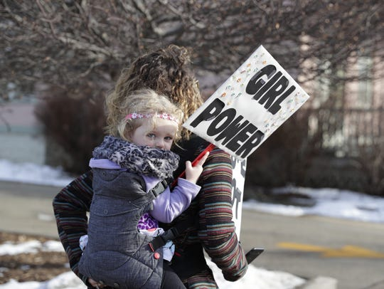 Peighton Letizia, 3, holds a 'girl power' sign during