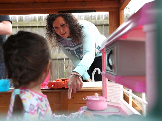 Alyssa Higgins plays outside with a 3-year-old foster daughter at the family home on Friday, Jan. 26, 2018. The care agency preferred that the faces and names of the children were kept private.