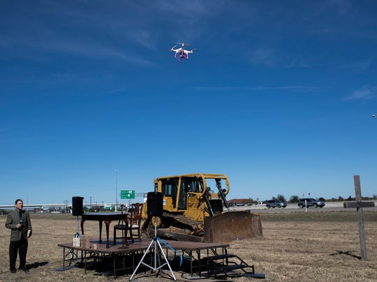 Pastor Richard Milby watches a drone climb to the altitude of 230 feet to demonstrate the hight of the proposed Corpus Christi Cross during a contract signing ceremony Monday, Jan. 29, 2018, near Carbon Plant Road and Interstate 37.
