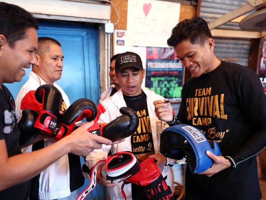 Jerwin Ancajas (right), of the Philippines, signs boxing gear before working out Tuesday, Jan. 30, 2018, at the Neighborhood Boxing Center in Corpus Christi ahead of Saturday's Top Rank boxing card at the American Bank Center. He will fight Israel Gonzalez (Mexico) for the IBF World Junior Bantamweight Title.