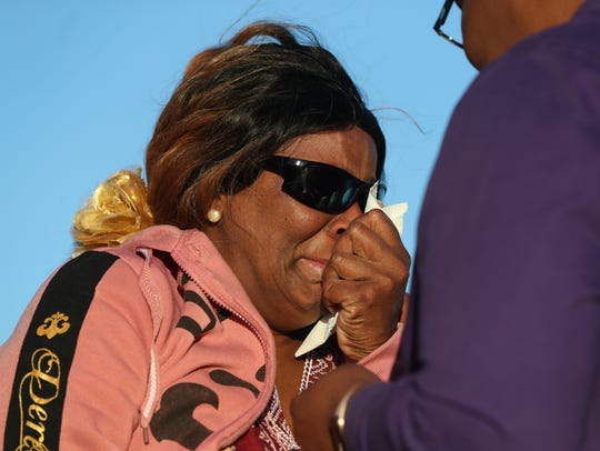 Vanessa Henry wipes away her tears as she gathers her