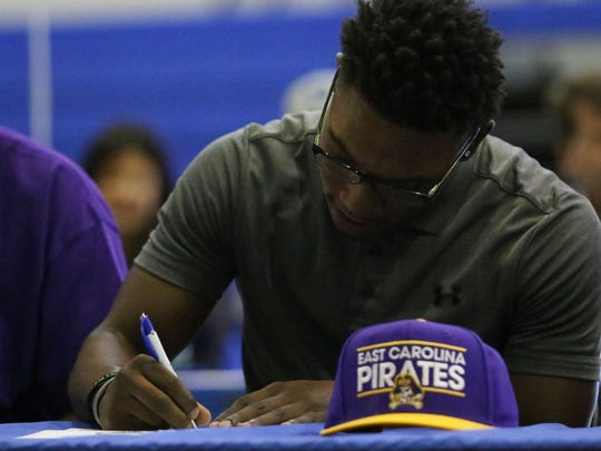 Community School of Naples senior Tay Williams signs his letter of intent to play football for East Carolina University during National Signing Day on Feb. 7, 2018.