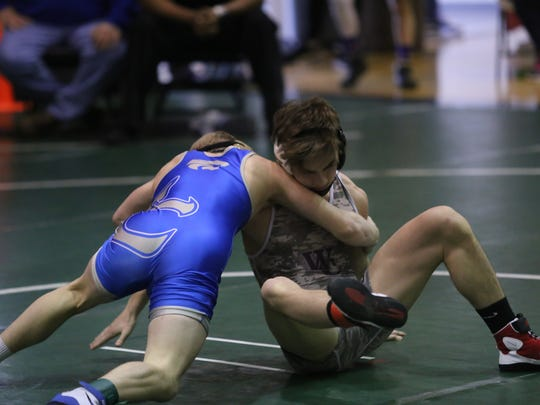 West Creek's Tristan Entwistle (right) tries to stay upright as he competes in the 113-pound Region 6 championship match Saturday at Kenwood High.