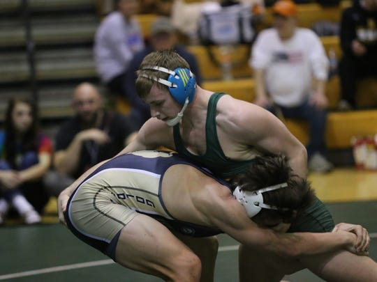 Northwest's Blake Spink bears down on his opponent during their 160-pound championship match Saturday at Kenwood High.