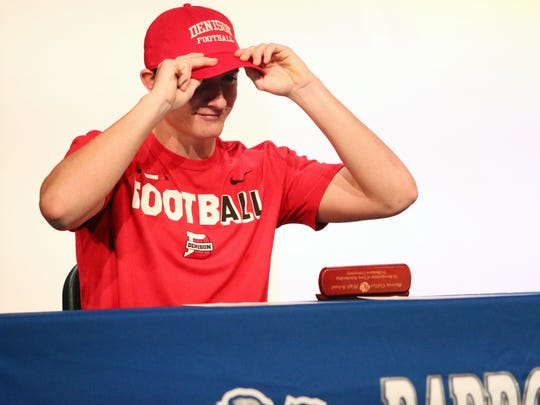 Senior Jacob Kuhlman puts on his hat after signing to play football with Denison University during Barron Collier High School's signing ceremony on Thursday, Feb. 15, 2018.