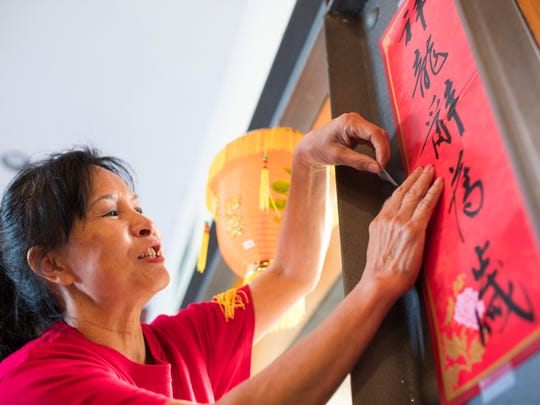 Yalee Shih hangs up a banner Thursday, Feb. 15, 2018 in preparation for the Taste of Asia and Lunar New Year Celebration that will happen this Saturday at the Texas State Muesum of Asian Cultures.