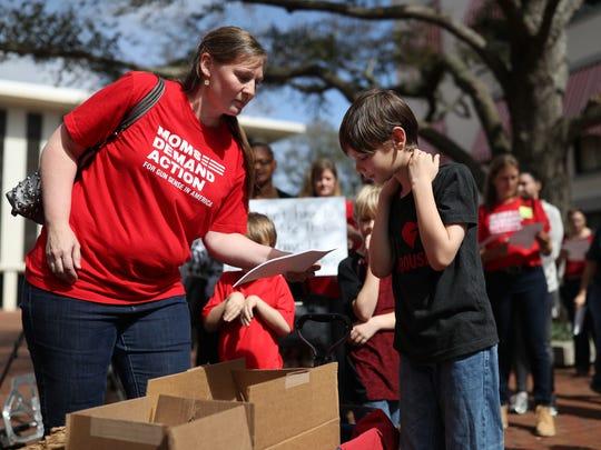 Gretchen Griffin and her son Jude, 10, pick up gun