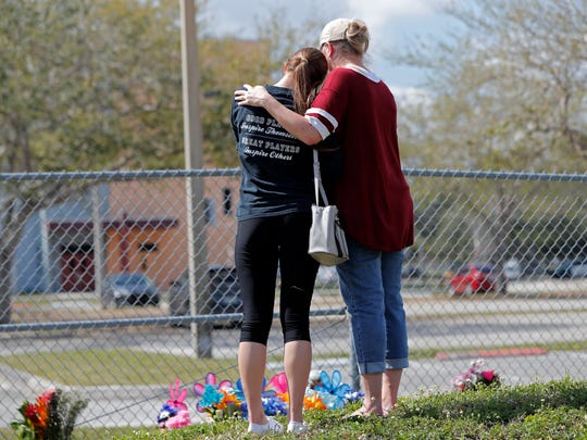 Hadley Sorensen, 16, a student at Marjory Stoneman Douglas High School, is comforted by her mother Stacy Sorensen at a makeshift memorial outside the school in Parkland, Fla., on Feb. 18, 2018.